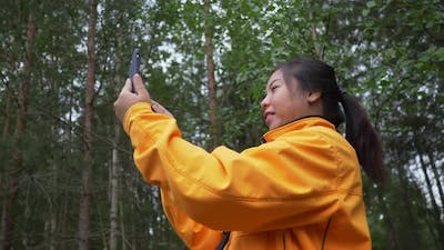Asian woman taking video call in the forest