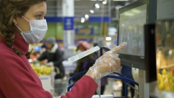 Thumbnail for Woman in Gloves and Mask Presses Finger on Touch Screen Electronic Scales in Supermarket