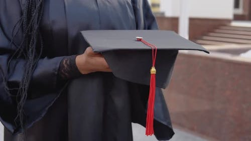 Master's Hat with a Red Tassel on the Hand of a University Graduate