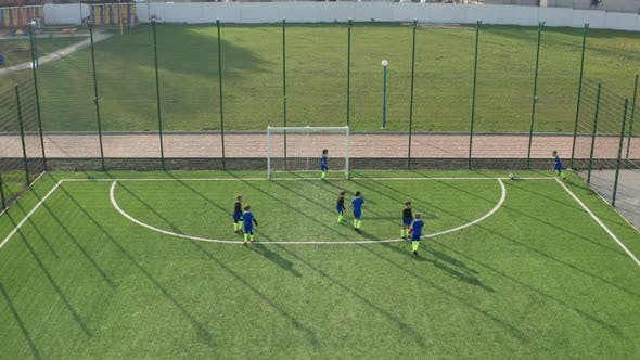 Kids Soccer Team Playing on Green Football Field