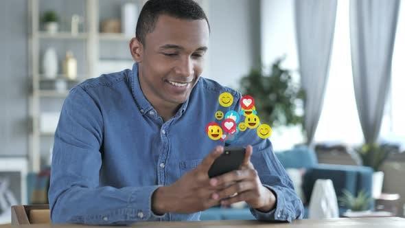 Thumbnail for Glücklicher afrikanischer Mann mit Smartphone, Emojis, Smileys und Likes