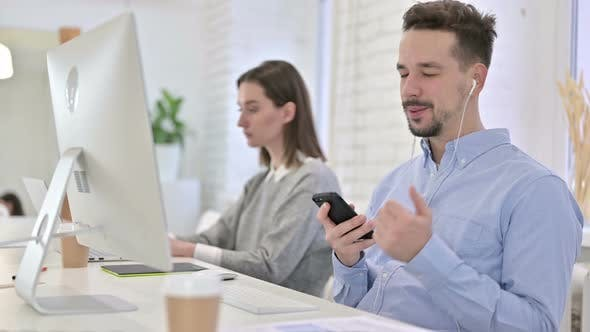 Thumbnail for Creative Male Professional Listening To Music on Smartphone in Office