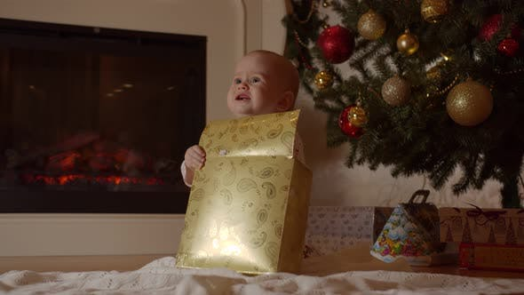 A Baby Is Unpacking a Christmas Present By the Tree