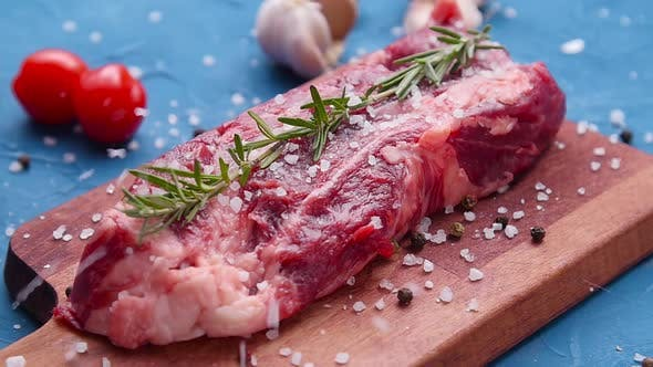 Raw Fresh Meat Steak with Herbs and Spices on Rustic Background