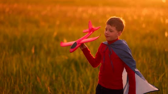 Thumbnail for The Boy Presents Himself As a Pilot and Runs Into the Field at Sunset with a Plane