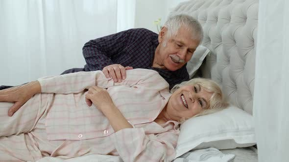 Thumbnail for Senior Caucasian Grandparents Couple Lying in Bed at Home in Morning. Man Gently Whispering To Woman