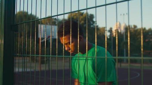 Überlegender Basketballspieler stehend auf Platz im Freien