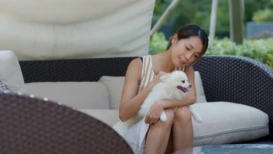 Thumbnail for Woman play with her pomeranian dog at resort house