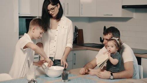 Junge glückliche Familie kocht gemeinsam Abendessen in der Küche