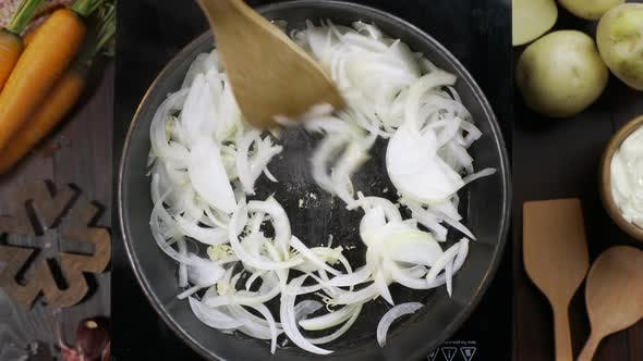 Thumbnail for Flat Lay Video: Chef Stirs Chopped Onion By Wooden Kitchen Spatula on the Hot Pan, Tabletop