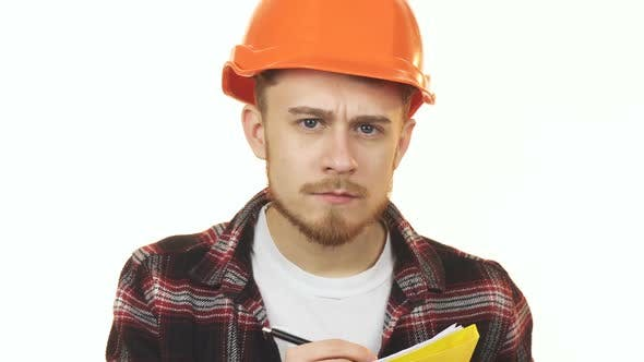 Thumbnail for Young Professional Male Architect in a Hardhat Making Notes