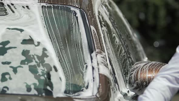 Thumbnail for Luxury Car Covered in Soap, Male Hand Washing It with Sponge, Carwash Service