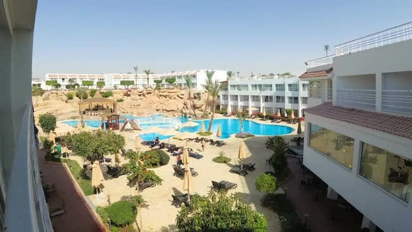 Time Lapse of Hotel Resort with Blue Swimming Pool, Umbrellas and Sunbeds in Egypt