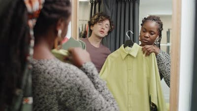 Assistant Helping Young Afro Woman in Dressing Room