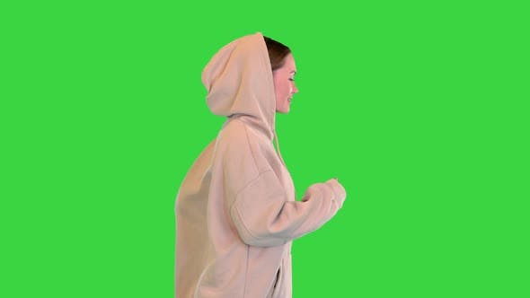 Young Woman Running in a Hoodie Running on a Green Screen Chroma Key