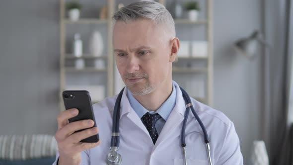 Thumbnail for Senior Doctor Browsing on Smart Phone