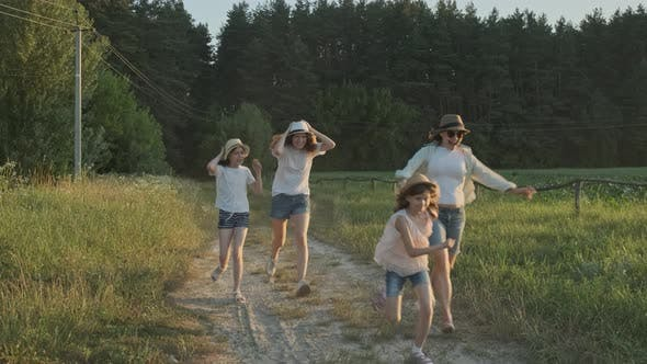 Cover Image for Happy Mother and Three Daughters Running Along a Country Road