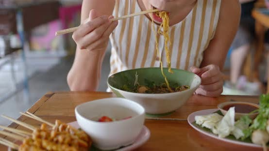 Thumbnail for Woman eat with thai cuisine boat noodle at outdoor vendor store