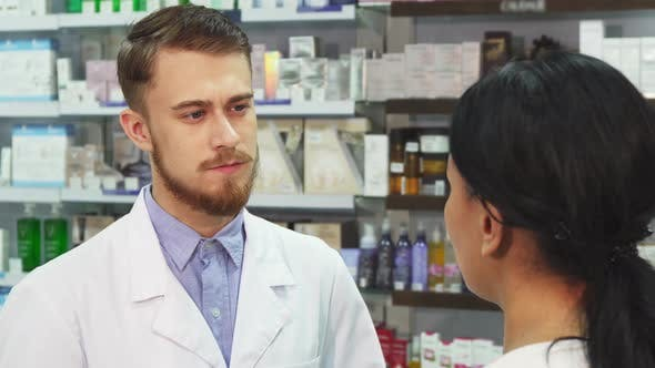 The Pharmacist Listens Attentively To His Client