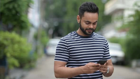Young Happy Bearded Indian Man Using Phone Outdoors