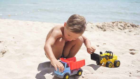Cute Child, Boy Playing with Cars on a Sandy Beach, Plastic Toy Car, Excavator. A Child and the