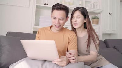 Asian couple using laptop for search web in living room at home, sweet couple enjoy love moment.