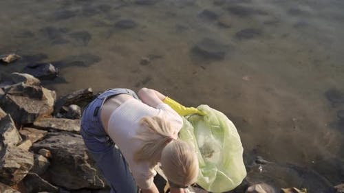 Young Woman Volunteer Collects Trash at the Lake