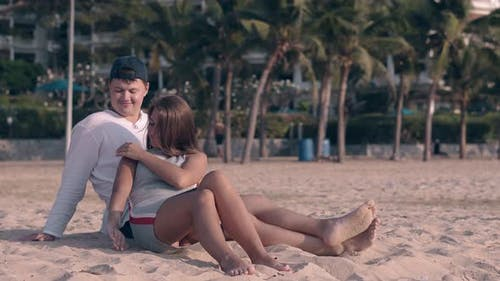 Guy and Girl Spend Time on Ocean Beach at Exotic Resort