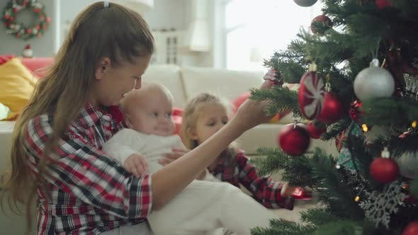 Thumbnail for Mother With Two Children Toddler And Preschooler Dress Up Christmas Tree