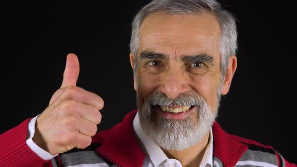 Thumbnail for An Elderly Man Smiles and Shows a Thumb Up To the Camera - Face Closeup - Black Screen Studio