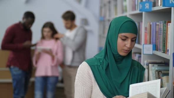 Thumbnail for Muslim Female Student Reading a Book in Library