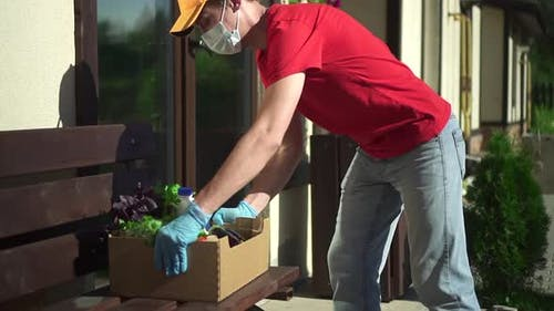 Lieferung von Lebensmitteln Während der Pandemie Freiwilliger in Maske und Handschuhen legen Sie Lebensmittelgemüse an der Tür Spld