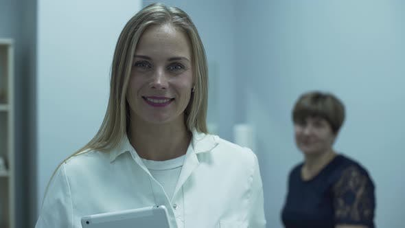 Thumbnail for Cute Professional Caucasian Doctor Smiling in Foreground Looking at the Camera While Her Mature
