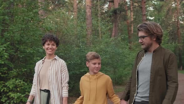 Young Family Of Three Strolling In Forest