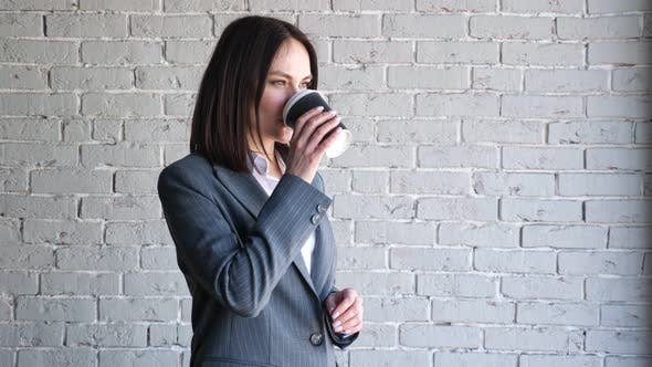 Smiling Company Manager in Blouse and Costume Drinks Coffee
