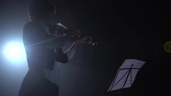 Thumbnail for Violinist Looks at the Notes and Plays . Silhouette. Black Smoke Background