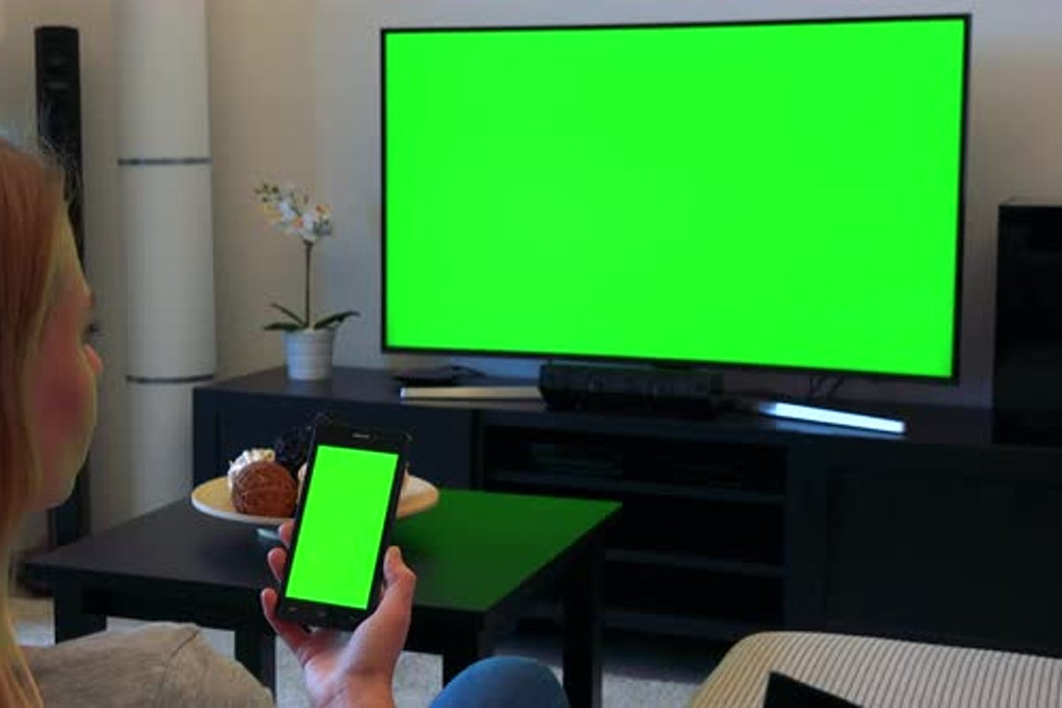Woman Sits On Couch In Living Room And Works On Green Screen Phone And Watches Tv By Thopter24 On Envato Elements