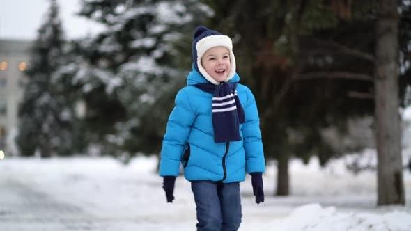Niedlich vier Jahre alt Junge in blau Winter Kleidung Spaziergänge in verschneite Straße