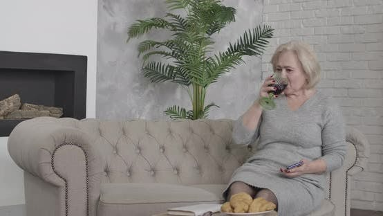 Thumbnail for Wealthy Senior Caucasian Woman Drinking Red Wine and Picking Up the Phone at Home. Portrait of