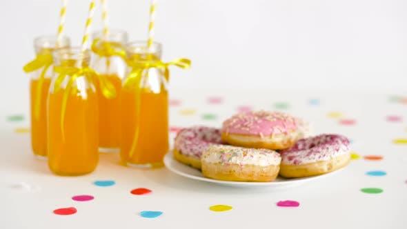 Donuts und Limonade oder Saft in Glasflaschen