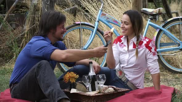 Thumbnail for Slow dolly shot of a young couple having an outdoor picnic
