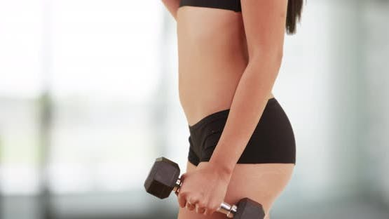 Latina woman lifting dumbbells