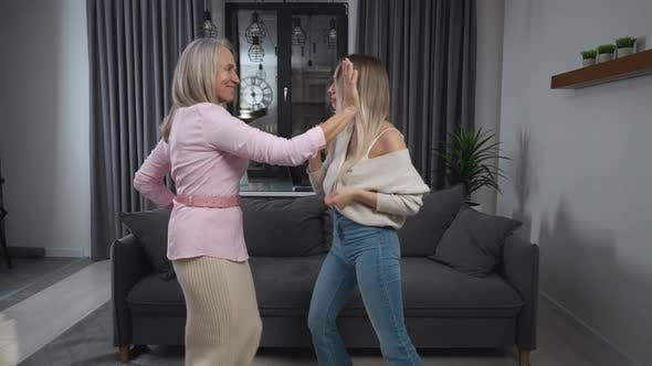 Granddaughter and Grandmother Dancing at Home in the Living Room Positive Mood Females Dance to the