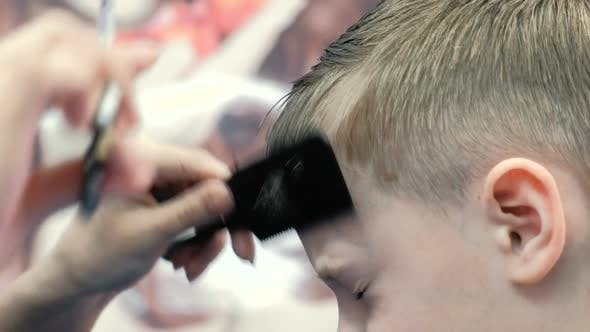 Thumbnail for Barber's Hands Combs and Cut Bangs on Blond Short Boy's Hair with Scissors