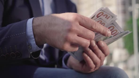 Close-up of Male Hands Counting Dollar Banknotes Outdoors on Sunny Day. Unrecognizable Wealthy Man