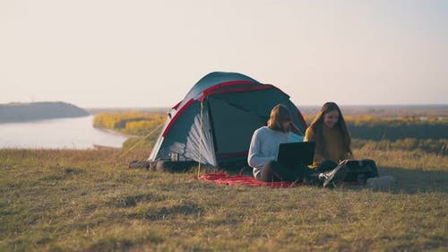 Joyful Girls with Tablet and Laptop on Red Plaid Near Tent