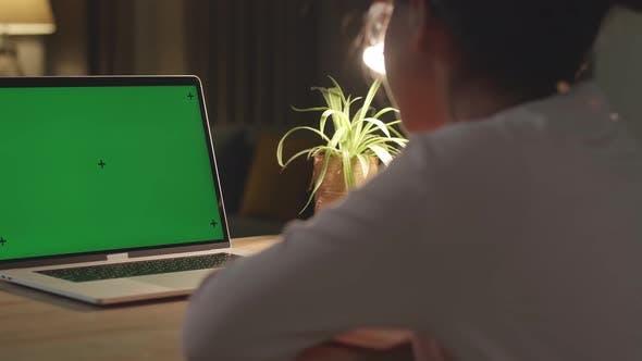 Teenager-Mädchen, das an ihrem Schreibtisch sitzt und lernt online auf einem Laptop mit grünem Mock-up-Bildschirm zu Hause
