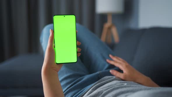 Thumbnail for Woman at Home Lying on a Sofa and Using Smartphone with Green Mock-up Screen in Vertical Mode. Girl