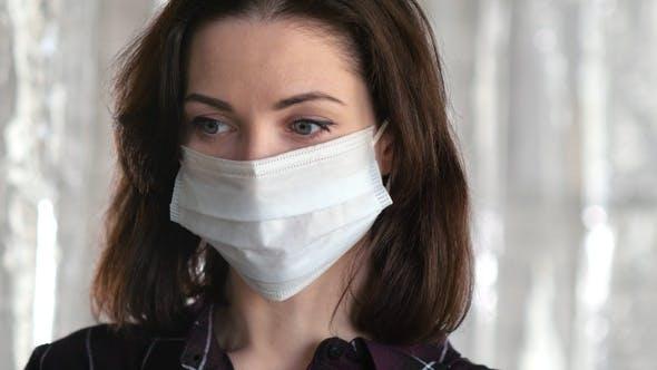 Thumbnail for Sad woman with face mask looking to camera. Coronavirus
