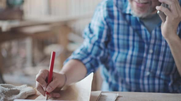 Asian senior male entrepreneur talking on mobile phone and listing order on paper at desk